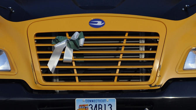 A green and white ribbon, the school colors of Sandy Hook Elementary School is seen attached to a bus on the first day of school after the holiday break, in Newtown, Conn., Wednesday, Jan. 2, 2013.  Nearly three weeks after the shooting rampage at Sandy Hook Elementary School in Newtown, students and teachers from the school will return to class Thursday in the neighboring town of Monroe. (AP Photo/Jessica Hill)