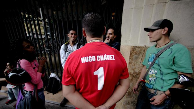 In this Jan. 22, 2013 photo, a supporter of Venezuela's President Hugo Chavez wears a T-shirt with the Chavez's name and the number one in Caracas, Venezuela. The cult of personality that Chavez long nurtured has been flourishing like never before as he confronts an increasingly difficult struggle against the mysterious cancer that afflicts him. (AP Photo/Fernando Llano)