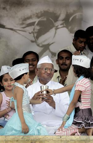 "India's anti-corruption activist Anna Hazare drinks coconut water and honey to  break his fast in  New Delhi, India, Sunday, Aug. 28, 2011. Hazare whose protest galvanizsed the nation's anger against corruption ended his 12 day hunger strike amidst thousands of supporters Sunday after forcing Parliament to throw its weight behind his crusade. Behind is the portrait of Mahatma Gandhi. Words on the caps of girls mean ""I am Anna."" (AP Photo/Manish Swarup)"