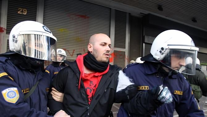 Riot police detain a protester from Labor Ministry in Athens, Wednesday, Jan. 30, 2013. Protesters from a Communist-back labor union forced their way into a government building and clashed with police who used tear gas to expel them. Members of the union are protesting planned reforms to the country's pension and income contribution system, part of ongoing austerity cuts demanded by Greece's euro partners and the International Monetary Fund who are keeping the country afloat with emergency loans. (AP Photo/Thanassis Stavrakis)
