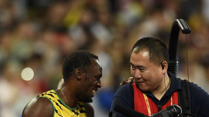 Usain Bolt of Jamaica chats with a cameraman after winning the men's 200 metres final during the 15th IAAF World Championships at the National Stadium in Beijing