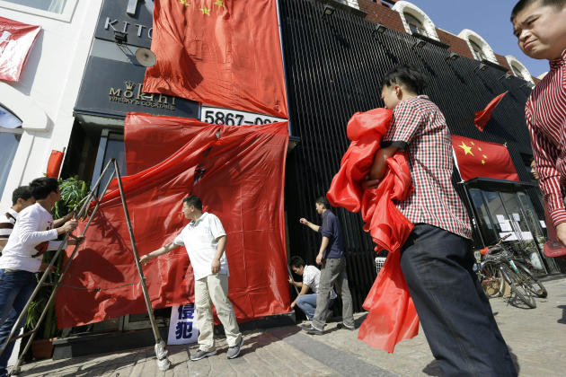 Workers at a Japanese restaurant cover up the shop front with Chinese national flags and red clothes ahead of major protests expected on Tuesday in Beijing, China, Monday, Sept. 17, 2012. Chinese are