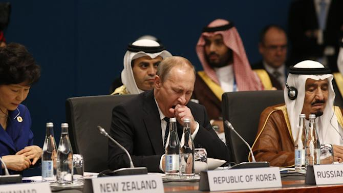 Russian President Vladimir Putin, center, yawns at the start of the plenary session at the G20 Summit in Brisbane, Australia Saturday, Nov. 15, 2014. Flanking Putin are South Korean President Park Geun-hye, left, and Saudi Arabia's Crown Prince Salman bin Abdulaziz Al Saud. As G-20 summit host Brisbane sweltered through a blistering heat wave, world leaders on Saturday got down to the business of cementing plans to drag a sagging global economy out of the doldrums. (AP Photo/Kevin Lamarque, Pool)