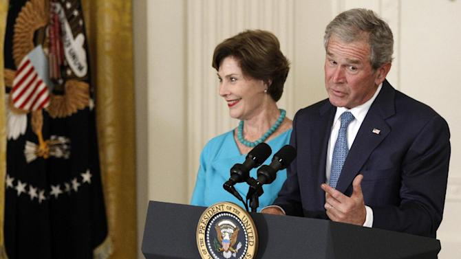 Former President George W. Bush, accompanied by former first lady Laura Bush, speaks in the East Room of the White House in Washington, Thursday, May 31, 2012, during the unveiling of their official portraits. (AP Photo/Charles Dharapak)