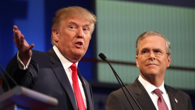 "FILE - In this Aug. 6, 2015, file photo, Republican presidential candidates Donald Trump and Jeb Bush participate in the first Republican presidential debate at the Quicken Loans Arena in Cleveland. Trump is going after Bush with a new campaign video about immigration. In the video, Bush is shown saying in a 2014 interview that illegal immigration is ""not a felony"" but rather an ""act of love.""  The video has images of three men who were in the country illegally and have been charged or convicted in killings. (AP Photo/Andrew Harnik, File)"
