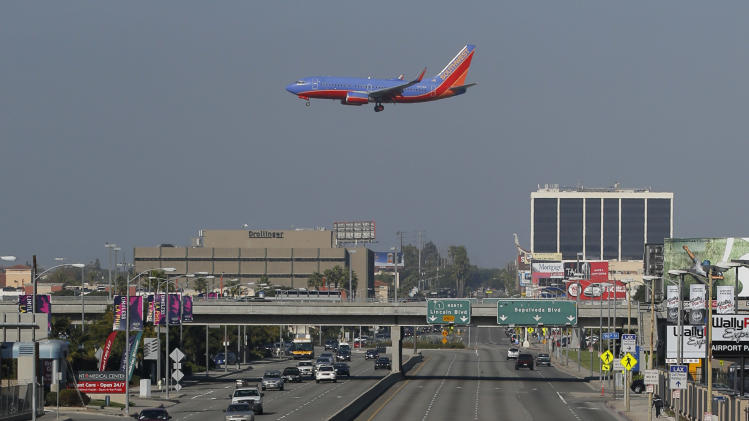 Union workers at Los Angeles International Airport march along the street near the airport in Los Angeles, Wednesday, Nov. 21, 2012. Hundreds of union members marched Wednesday near the entrance to Los Angeles International Airport, where Thanksgiving travelers were warned to arrive early in case of traffic snarls. (AP Photo/Jae C. Hong)