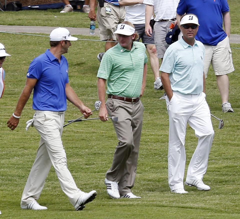 Dustin Johnson, left, Brandt Snedeker and Davis Love III walk up the No. 18 fairway at the St. Jude Classic golf tournament on Thursday, June 6, 2013, in Memphis, Tenn. (AP Photo/Rogelio V. Solis)