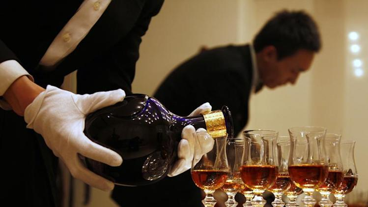 A waiter is reflected in a mirror as he pours luxury Scotch whisky Royal Salute into glasses in Beijing