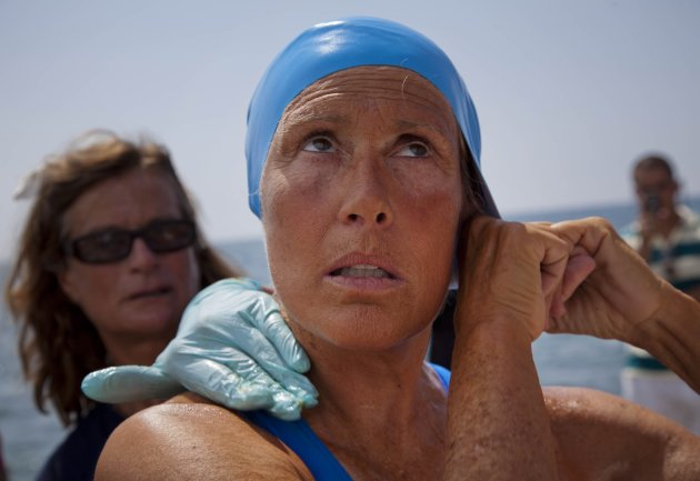 U.S. swimmer Diana Nyad adjusts her swimming cap as a woman applies a protective ointment to her skin as she prepares to jump into the water and start her swim to Florida from Havana, Saturday, Aug. 18, 2012. Endurance athlete Nyad launched another bid Saturday to set an open-water record by swimming from Havana to the Florida Keys without a protective shark cage. (AP Photo/Ramon Espinosa)