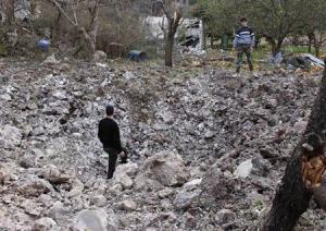 Free Syrian Army fighters inspect a crater caused by …
