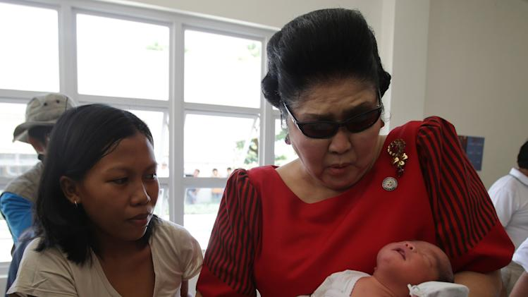 """In this May 5, 2013 photo, former Philippine First Lady Imelda Marcos, right, reacts as she carries a baby at a """"Mothering Center"""" in Ilocos Norte province, northern Philippines. Twenty-seven years after her dictator husband was ousted by a public revolt, Imelda Marcos has emerged as the Philippines' ultimate political survivor: She was back on the campaign trail this week, dazzling voters with her bouffant hairstyle, oversized jewelry and big talk in a bid to keep her seat in Congress. (AP Photo/Aaron Favila)"""