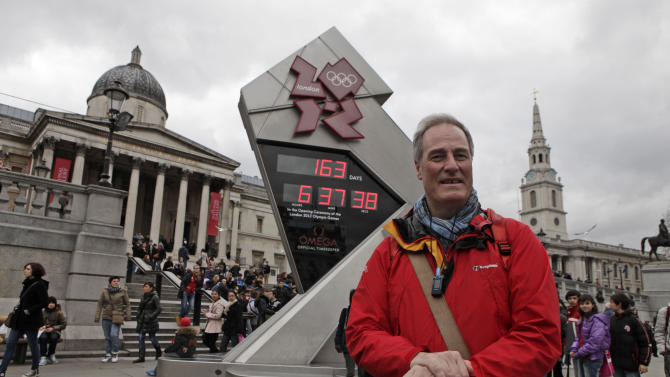 Britain's Lord Michael Bates poses for photographers in front of a clock showing the countdown to the 2012 London Olympic Games in Trafalgar Square, London, Wednesday, Feb. 15, 2012. Bates returned to Britain after walking 3,000 miles (4,800 kilometers) from Greece to promote peace during the Olympics. (AP Photo/Lefteris Pitarakis)