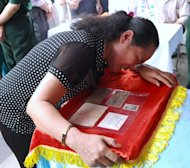 Vu Thi Tuyen cries over her late father Vu Dinh Doan's personal documents, including a frayed diary, handed over to her family during a ceremony held at her village in the northern province of Hai Duong