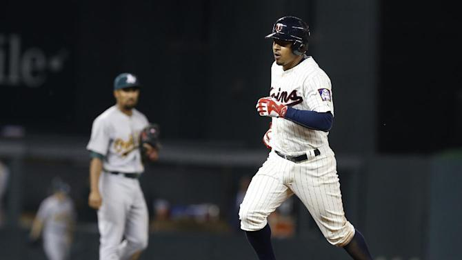 Minnesota Twins' Eduardo Escobar runs the bases on a three-run home run off Oakland Athletics starting pitcher Scott Kazmir in the sixth inning of a baseball game, Wednesday, May 6, 2015, in Minneapolis. The Twins won 13-0. Escobar also hit a two-run double in the seventh. (AP Photo/Jim Mone)
