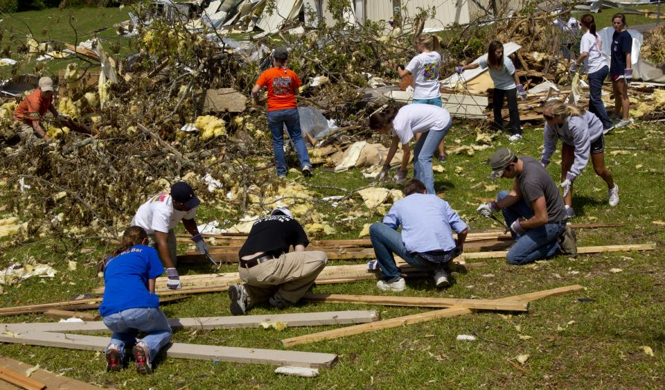 A group of Auburn students assist in the clean up of debris on Thursday, May 5, 2011 in Pleasant Grove, Ala. A tornado left a path of total devastation as it passed through on April 27. (AP Photo/Butch Dill)