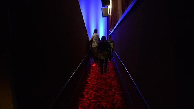 Guests enter theater XD at the Century Aurora cinema, formerly the Century 16, before a reopening and remembrance ceremony Thursday, Jan. 17, 2013 in Aurora, Colo. The theater is where 12 people were killed and dozens injured in a shooting rampage last July. (AP Photo/The Denver Post, RJ Sangosti, Pool)