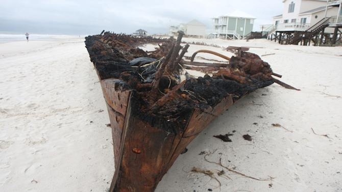 In this Wednesday, Sept. 5, 2012 photo, the ghostly remains of an old wooden ship rest along a private beach at Fort Morgan, Ala. The ship is the Rachel, a schooner built in Pascagoula, Miss., during World War I, according to Mike Bailey, historian with the Fort Morgan Historical Society. The ship was lost in a storm in 1923. The remains of the the Rachel have been uncovered by hurricanes in the past, but more of the wreck was revealed in the wake of Hurricane Isaac.  (AP Photo/Press-Register, Brian Kelly) MAGS OUT