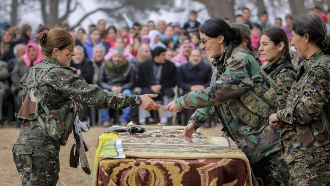A female fighter of the Kurdish People's Protection Units receives a military card at a military camp in Ras a-Ain