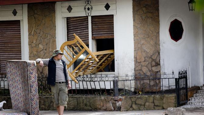 A man stands outside his home with his belongings as he waits for them to dry in La Plata, in Argentina's Buenos Aires province, Thursday, April 4, 2013. Buenos Aires Gov. Daniel Scioli says 49 people died in this flooded capital of Argentina's largest province as torrential rains swamped entire neighborhoods, washing away cars and flooding some houses to their rooftops. (AP Photo/Natacha Pisarenko)