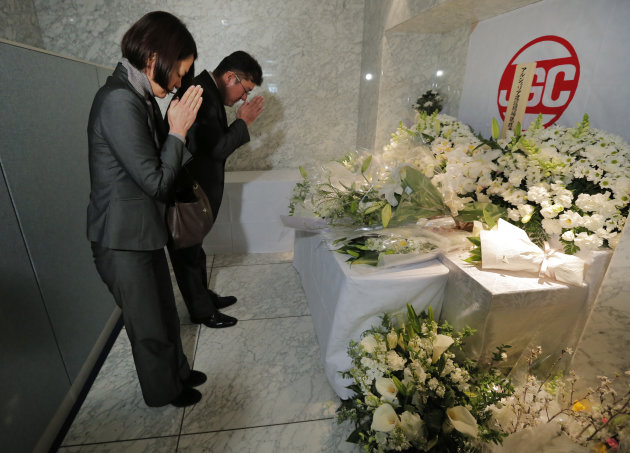 <p>               Mourners offer a prayer near bouquets left in honor of the Japanese employees of  JGC Corporation who died in the standoff at Ain Amenas gas plant in Algeria, at the company's headquarters in Yokohama, near Tokyo, Friday, Jan. 25, 2013.  Ten Japanese workers were killed among the 37 hostages who died in the attack. (AP Photo/Itsuo Inouye)