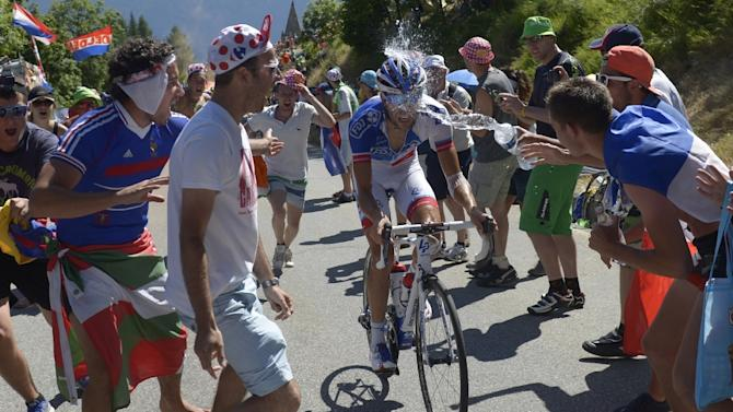 A fan sprays water on France's Thibaut Pinot as he rides in the Tour de France cycling race on July 25, 2015