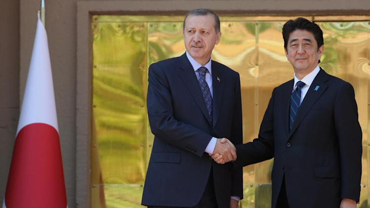 Japanese Prime Minister Shinzo Abe, right, and his Turkish counterpart Recep Tayyip Erdogan shake hands during a ceremony in Ankara, Turkey, Friday May 3, 2013. (AP Photo/Burhan Ozbilici)