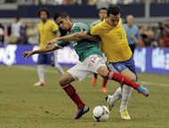 Forward Leandro Damiao of Brazil (R) and defenseman Severo Meza of Mexico battle for position during the first half of a soccer game at Cowboys Stadium in Arlington, Texas. Manchester United striker Javier Hernandez and Tottenham Hotspur playmaker Gio Dos Santos scored to give Mexico a 2-0 victory over Brazil in an international football friendly on Sunday