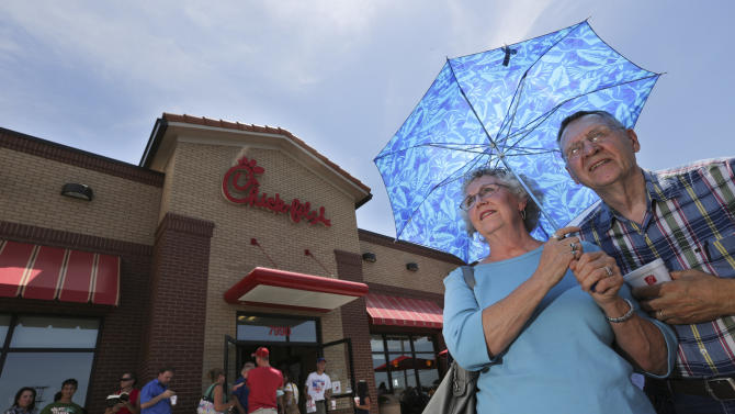 """Don and Brenda Nichols shield themselves from 100 degree temperatures as they stand in line for a Chick-fil-a meal at the chain's restaurant in Wichita, Kan., on Wednesday. Aug. 1, 2012. Over 200 people waited in line to buy a meal to show their support for the company that's currently embroiled in a controversy over same-sex marriage.   Former Arkansas Gov. Mike Huckabee, a Baptist minister, declared Wednesday national """"Chick-fil-A Appreciation Day."""" Opponents of the company's stance are planning """"Kiss Mor Chiks"""" for Friday, when they are encouraging people of the same sex to show up at Chick-fil-A restaurants around the country and kiss each other. (AP Photo/The Wichita Eagle, Travis Heying)"""
