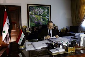 Faisal Muqdad poses in his office following an interview…