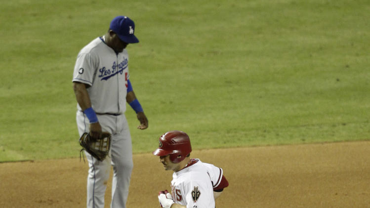 Arizona Diamondbacks' Xavier Nady, right, rounds the bases after hitting a three run home run as Los Angeles Dodgers' Juan Uribe looks down during the seventh inning of a baseball game Friday, July 15, 2011, in Phoenix. (AP Photo/Matt York)