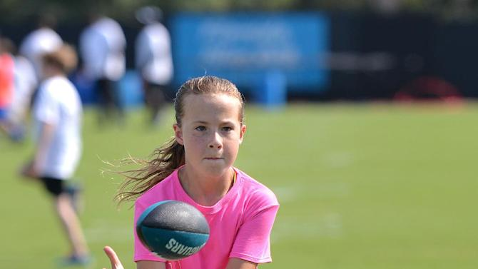 Merridy Archambault, 10, catches a pass while working with the wide receivers at an NFL football Jacksonville Jaguars' Got Skills Rookie Day on Friday, June 20, 2014, in Jacksonville, Fla