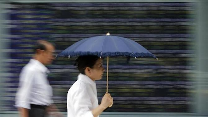 A woman holding a parasol walks past a stock quotation board outside a brokerage in Tokyo July 19, 2013. REUTERS/Toru Hanai/Files