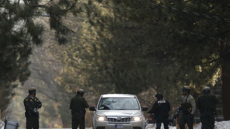 San Bernardino County sheriff's deputies search a car in Big Bear, Calif, Thursday, Feb. 7, 2013. An ex-Los Angeles police officer who authorities say went on a killing spree to punish those he blamed for his firing killed three people, set off a manhunt that stretched across three states and into Mexico, and stirred fear throughout the region. (AP Photo/Jae C. Hong)