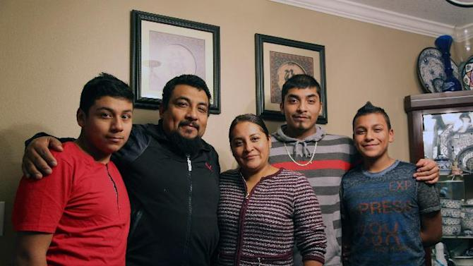 In this photo taken on Thursday, Nov. 20, 2014 in Aloha, Oregon, the Romero-Morales family, from left to right, Kevin, Jorge, Clara, Alan, and Naethan, pose for a picture in their home's dining room after President Obama's televised announcement on immigration. The parents, Clara and Jorge, will likely qualify for relief from deportation, because two of their sons are U.S. citizens _ but they are afraid the relief might only be temporary, and Republicans could eventually take it away. (AP Photo/Gosia Wozniacka)