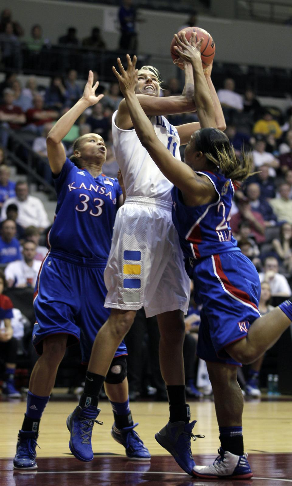 Delaware's Elena Delle Donne (11) is pressured under the basket by Kansas' Tania Jackson (33) and Cece Harper (24) during the first half of an NCAA tournament second-round women's college basketball game in Little Rock, Ark., Tuesday, March 20, 2012. (AP Photo/Danny Johnston)