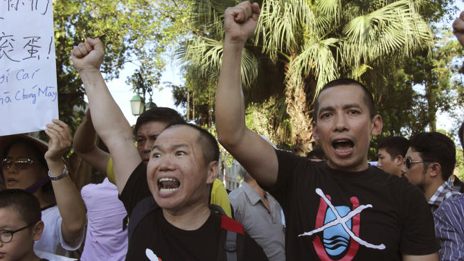 Vientnamese protesters chant anti-China slogans in Hanoi, Vietnam Thursday June 19, 2014. China said Thursday it is moving a second oil rig closer to Vietnam's coast. Vietnamese authorities broke up a small protest against the Chinese move on Thursday. About a dozen people gathered at a park in central Hanoi. (AP Photo/Tran Van Minh)