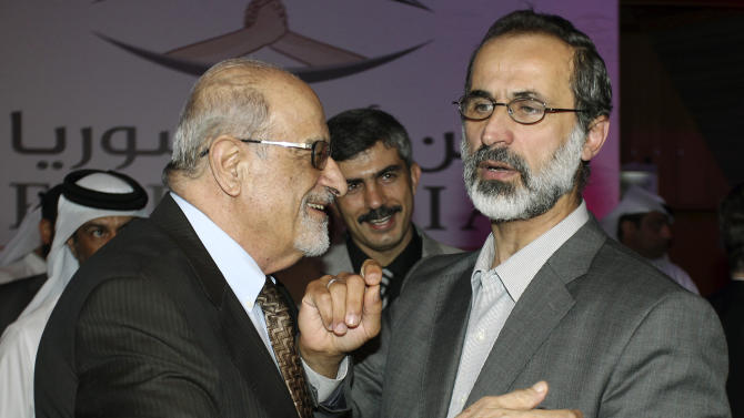 In this Sunday, Nov. 11, 2012 file photo, Syrian opposition figure and prominent Syrian human rights activist Haytham al-Maleh, left, congratulates Muslim cleric Mouaz al-Khatib after he was elected president of the newly formed Syrian National Coalition for Opposition and Revolutionary Forces, in Doha, Qatar. While lacking in political experience, Al-Khatib, the 52-year-old preacher-turned-activist is described by Syrians as a man of the people--a modest, unifying figure who commands wide respect among the country's various opposition groups and rebels. (AP Photo/Osama Faisal)