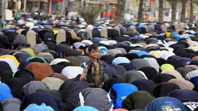 A young boy attends Friday prayers in the Shiite stronghold of Sadr City in Baghdad, Iraq, Friday, Feb. 15, 2013. (AP Photo/ Karim Kadim)