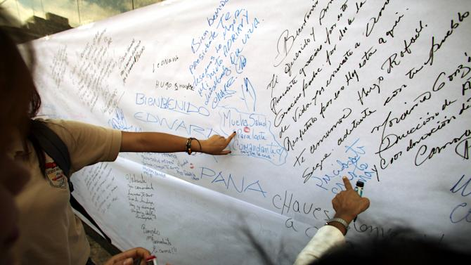 Supporters of Venezuela's President Hugo Chavez point and read aloud welcome and get well messages written on pieces of paper taped to a wall near Bolivar Square in Caracas, Venezuela, Monday, Feb. 18, 2013. Chavez returned to Venezuela early Monday after more than two months of treatment in Cuba following cancer surgery, his government said, triggering street celebrations by supporters who welcomed him home while he remained out of sight at the Carlos Arvelo Military Hospital in Caracas, where he will continue his treatment. (AP Photo/Fernando Llano)