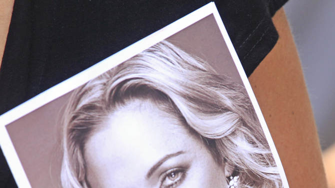 A woman holds a photo of Reeva Steenkamp, as she leaves her funeral in Port Elizabeth, South Africa, Tuesday, Feb. 19, 2013. Olympic athlete Oscar Pistorius is charged with the premeditated murder of Steenkamp on Valentine's Day. The defense lawyer says it was an accidental shooting. (AP Photo/Schalk van Zuydam)