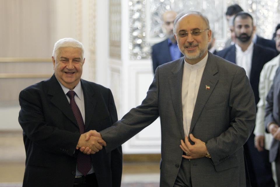 Iranian Foreign Minister Ali Akbar Salehi, right, shakes hands with his Syrian counterpart Walid al-Moallem, prior to their joint press conference, in Tehran, Iran, Sunday, July 29, 2012. (AP Photo/Vahid Salemi)