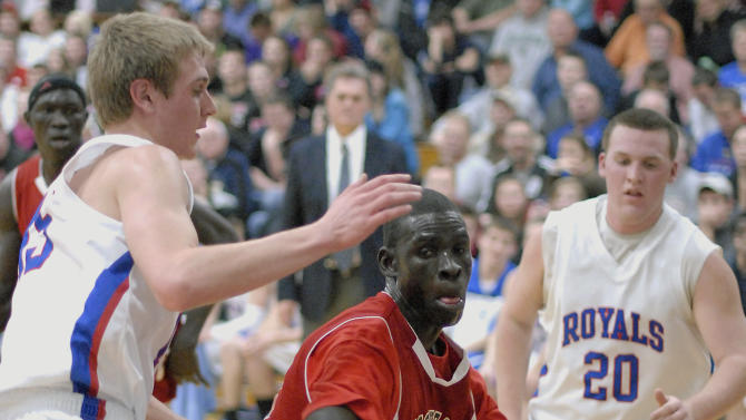 In this Dec. 5, 2012 photo, Mooseheart High School's Mangisto Deng, center, maneuvers around Hinckley-Big Rock's Nick Gentry, left, under the hoop in a high school basketball game in Hinckley, Ill. Deng is one of four Sudanese athletes who find themselves center court of a controversy in suburban Chicago over high schools recruiting athletes. The Illinois High School Association board will consider Monday, Dec. 10 whether the three basketball players and a cross-country runner are ineligible to continue competing for Mooseheart. The century-old school says it accepted the students as part of its tradition of helping troubled and poor students, but the ISHA's executive director determined that it broke a prohibition against recruiting athletes after accepting the young men from an Indiana outfit called A-HOPE, an Indiana-based foundation whose founder has drawn NCAA scrutiny. (AP Photo/Daily Herald, Laura Stoecker)