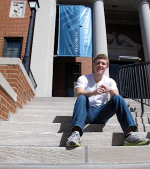 """This photo taken Sept. 20, 2012 shows Abraham Mulberry, an 18-year-old freshman, sitting on a campus hall step at Elmhurst College in Elmhurst, Ill. What a difference four years can make. In 2008, college campuses were filled with campaign posters and political rallies _ and frenzy. Remember """"Obamamania?"""" This year, it's difficult to find a college student who's truly excited about the presidential race.  (AP Photo/Martha Irvine)"""