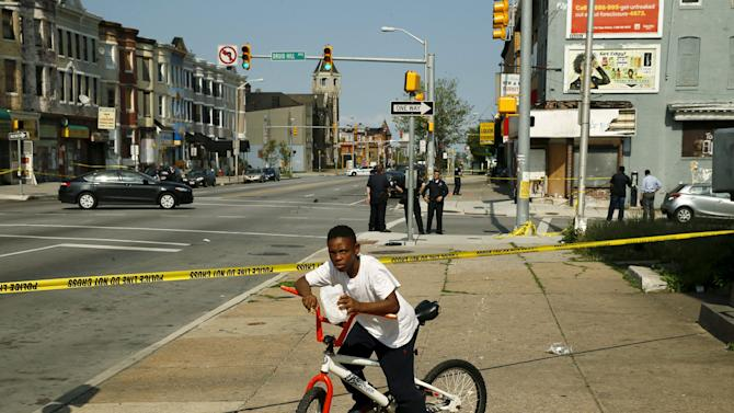 A young boy, who lives in the neighborhood where Freddie Gray, is stopped by police tape at the scene of a shooting in West Baltimore