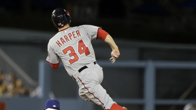 Washington Nationals Bryce Harper steals second and heads for third on an error throw to Los Angeles Dodgers shortstop Dee Gordon in the fifth inning of a baseball game in Los Angeles Monday, May 13, 2013. (AP Photo/Reed Saxon)