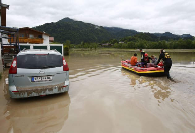 Rescue workers pull a boat next to a damaged car in the flooded western Austrian village of Koessen
