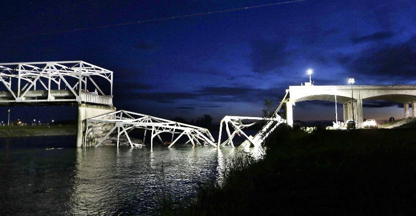 The collapsed Interstate-5 bridge is seen at dusk submerged after collapsing into the Skagit River, dumping vehicles and people into the water, in Mount Vernon, Wash., Thursday, May 23, 2013. (AP Photo/Elaine Thompson)