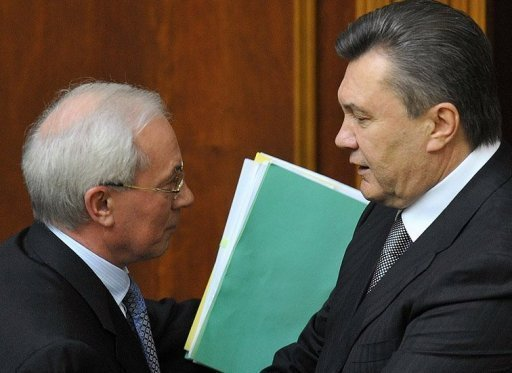 <p>Ukrainian President Viktor Yanukovych (right) greets Prime Minister Mykola Azarov after a 2010 parliamentary session in Kiev. Yanukovych has accepted the resignation of Azarov and the entire government.</p>