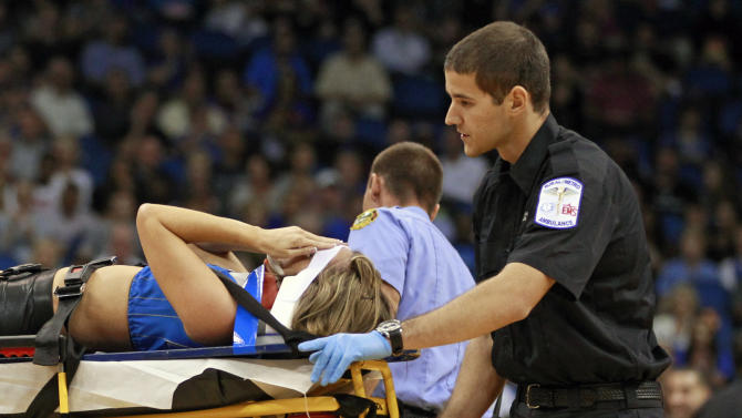 Jamie Woode, a former college cheerleader and Magic Stunt Team member, fell during a routine and was wheeled off the floor on a stretcher during the first half of an NBA basketball game between the Orlando Magic and the New York Knicks, Tuesday,Nov. 13, 2012, in Orlando, Fla. She was transferred to a nearby hospital where she was breathing on her own and moving her extremities, according to paramedics who attended to her.(AP Photo/John Raoux)