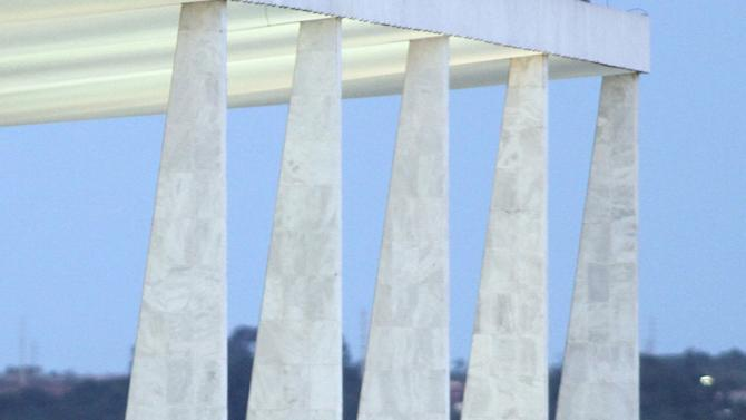 The coffin containing the remains of Brazilian architect Oscar Niemeyer is carried down the ramp of the Planalto presidential palace at the end of a memorial, in Brasilia, Brazil, Thursday, Dec. 6, 2012. Niemeyer, 104, the groundbreaking architect who designed Brazil's futuristic capital and much of the United Nations complex, died Wednesday night in Rio de Janeiro, the seaside city where he was born and where his remains will be buried Friday afternoon. (AP Photo/Eraldo Peres)